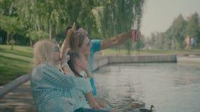 采取在巧妙的电话的愉快的家庭selfie由湖 股票视频