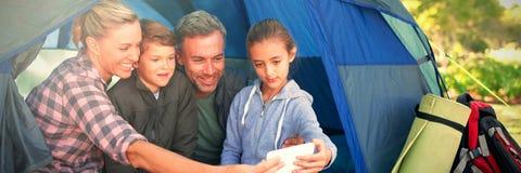 采取在帐篷的家庭一selfie在露营地 图库摄影