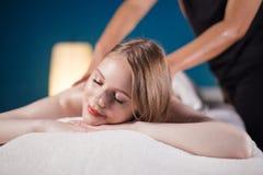 采取在按摩床上的少妇乐趣,与眼睛关闭了 妇女 温泉沙龙 库存照片