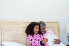采取在数字式片剂的祖母和孙女selfie在床屋子里 库存图片