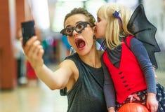 采取在数字式pho的母亲和女儿可怕万圣夜selfie 免版税库存图片