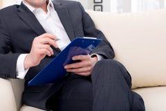 商人坐有文件夹的长沙发 免版税图库摄影