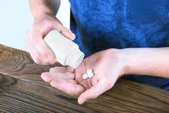 采取在明亮的背景的男性药片 Prescripted药物,阿斯匹灵,止痛药 配药治疗 自杀预防 免版税库存图片