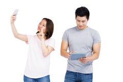 采取在智能手机的一selfie和人的少妇使用数字式片剂 免版税库存照片