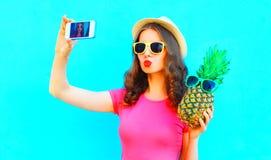 采取在智能手机的凉快的女孩图片自画象用菠萝 图库摄影