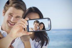 采取在智能手机的夫妇selfie 免版税库存照片