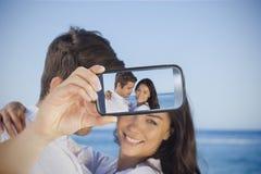 采取在智能手机的夫妇selfie 免版税库存图片