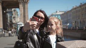 采取在智能手机的母亲和女儿少年selfie画象在城市 家庭、旅行和旅游业概念 影视素材