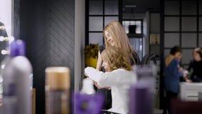 采取在智能手机的白肤金发的美容师一selfie有她的客户的在构成会议期间,愉快的白肤金发的妇女 影视素材