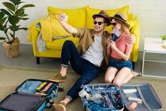 采取在智能手机的美好的夫妇selfie,当包装手提箱时 免版税库存图片