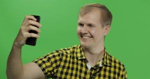 采取在智能手机的黄色衬衣的白种人年轻人好的selfies 免版税库存图片