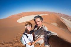采取在沙丘的成人夫妇selfie在Sossusvlei在纳米比亚沙漠, Namib Naukluft国家公园,主要旅行目的地 免版税库存照片