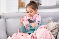 采取在沙发的女孩咳嗽糖浆 免版税图库摄影