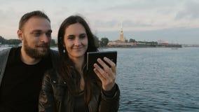 采取在河和城市背景的美好的年轻夫妇selfie  圣彼德堡 4K 免版税库存图片