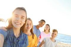 采取在海滩的小组孩子selfie 图库摄影