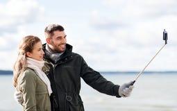 采取在海滩的愉快的夫妇selfie在秋天 免版税库存照片