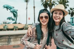 采取在海豚喷泉前面的妇女selfies 免版税图库摄影