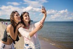 采取在海滩的两个愉快的女孩selfie获得乐趣 库存照片