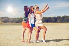 采取在海滩的小组微笑的妇女selfie 免版税库存照片