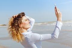 采取在海滩的年轻白肤金发的妇女一selfie 库存照片