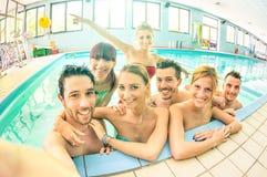 采取在游泳池的最好的朋友selfie -愉快的友谊 库存图片