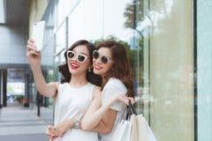 采取在滑稽的面孔的最好的朋友妇女selfie拿着佩带时髦时尚的顾客穿衣 免版税库存照片