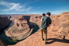 采取在照相机的照片和三脚架的旅游人在他的旅行期间在大峡谷,美国 图库摄影