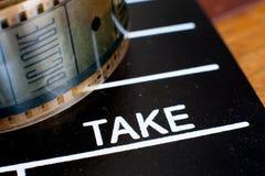 采取在电影拍板和影片轴的标签 免版税图库摄影