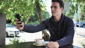 采取在电话的年轻人Selfie,当坐在咖啡馆大阳台时 影视素材