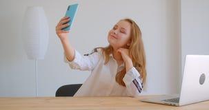 采取在电话的年轻俏丽的白种人女孩特写镜头画象selfies坐在膝上型计算机前面户内  股票视频