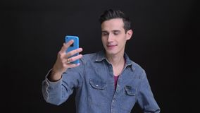 采取在电话的年轻白种人人特写镜头画象selfies有在黑色隔绝的背景 股票视频