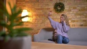 采取在电话的成人白种人白肤金发的女性特写镜头射击selfies,当坐长沙发户内在舒适时 股票录像