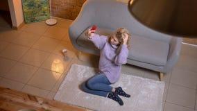 采取在电话的成人白种人白肤金发的女性特写镜头顶面射击selfies,当坐长沙发户内在时 影视素材