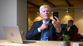 采取在电话的老白种人商人特写镜头射击selfies坐在膝上型计算机前面户内在 股票视频