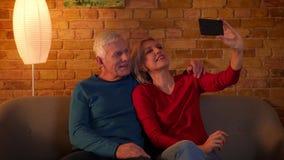 采取在电话的资深夫妇特写镜头射击selfies微笑愉快地坐长沙发户内在舒适 影视素材