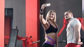 采取在电话的运动夫妇selfies在健身房 库存照片