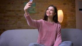 采取在电话的selfies和在长沙发的年轻俏丽的深色的白种人女性特写镜头射击微笑的开会  股票录像
