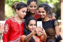 采取在电话,浦那,马哈拉施特拉的小组穿着体面的女孩selfies 库存照片