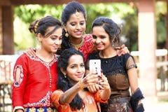 采取在电话,浦那,马哈拉施特拉的小组穿着体面的女孩selfies 免版税图库摄影