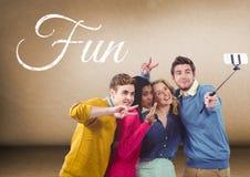 采取在空白的棕色背景前面的小组朋友selfie与乐趣文本 库存图片