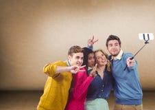 采取在空白的棕色背景前面的小组朋友selfie 库存照片