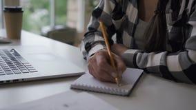采取在笔记本的女性企业主设计师的手笔记 女推销员 股票录像