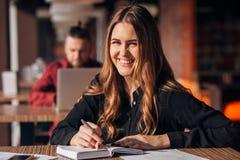 采取在笔记薄的一名确信的妇女的画象笔记,当坐在咖啡馆的桌上户内和看时 免版税图库摄影