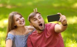 采取在绿草的年轻夫妇selfie在公园 免版税库存照片