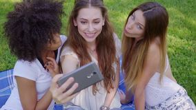 采取在草坪的俏丽的女孩selfie 影视素材