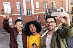 采取在街道的小组愉快的朋友一selfie 免版税库存图片