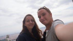 采取在观察台的一对年轻夫妇一selfie 巴塞罗那市鸟瞰图 城市概要 免版税库存照片