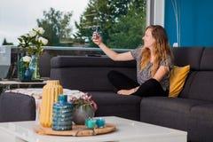 采取在长沙发的年轻女人一selfie 免版税库存照片