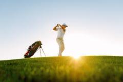 采取在高尔夫球场的男性高尔夫球运动员射击 免版税库存图片
