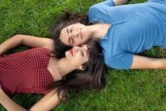 采取在绿草的年轻夫妇休息 免版税库存图片